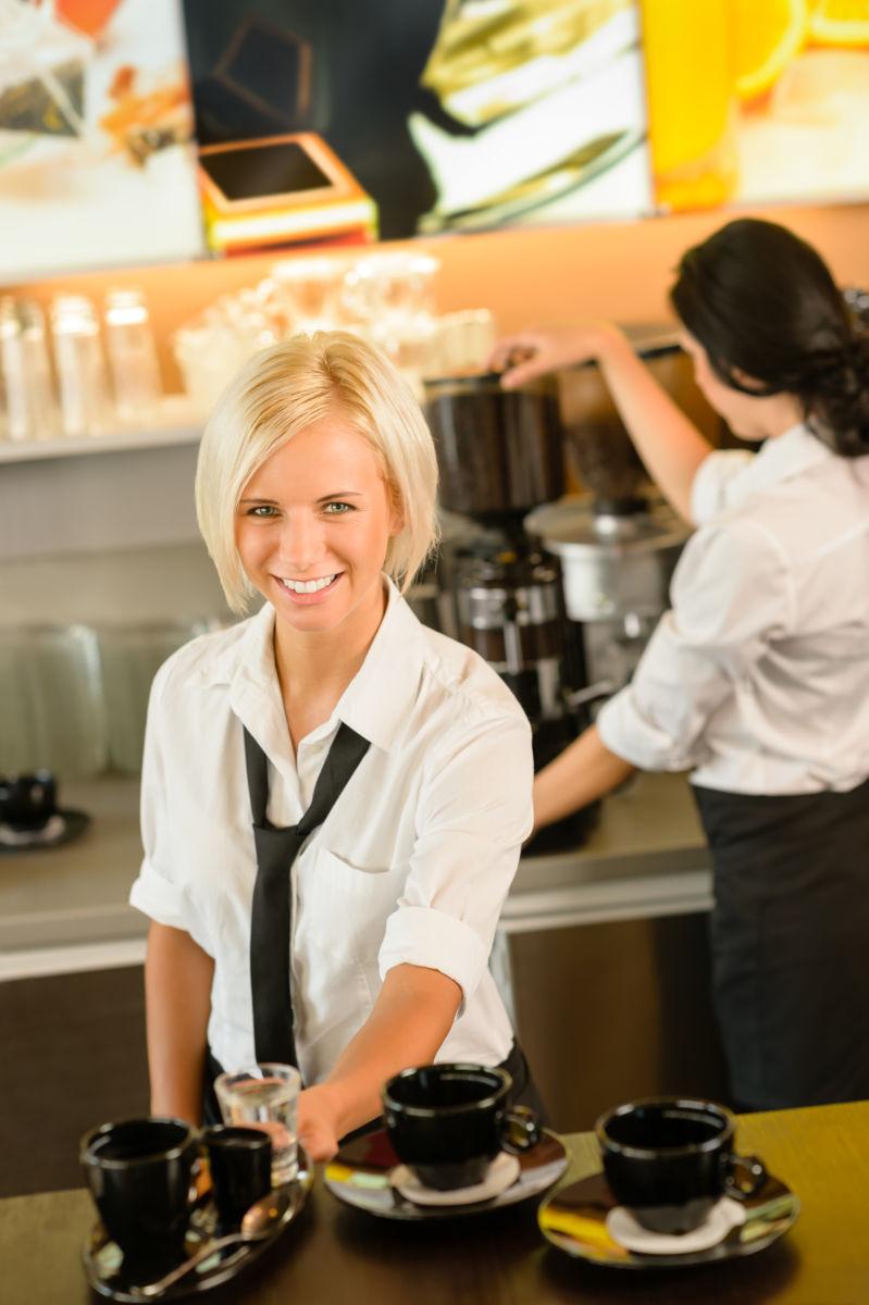 Auszubildende serviert Kaffeespezialität