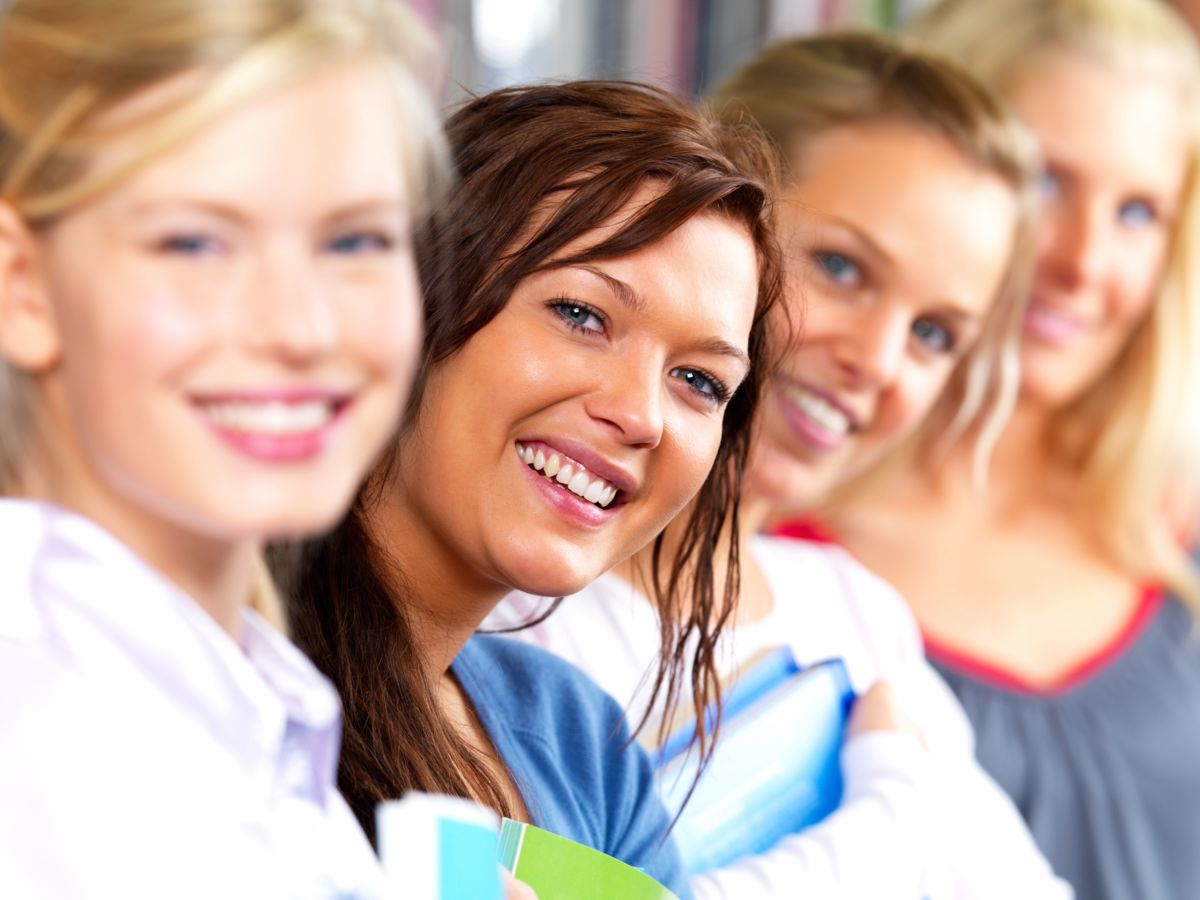 Closeup portrait of beautiful women smiling together sitting in a line attending a meeting in college