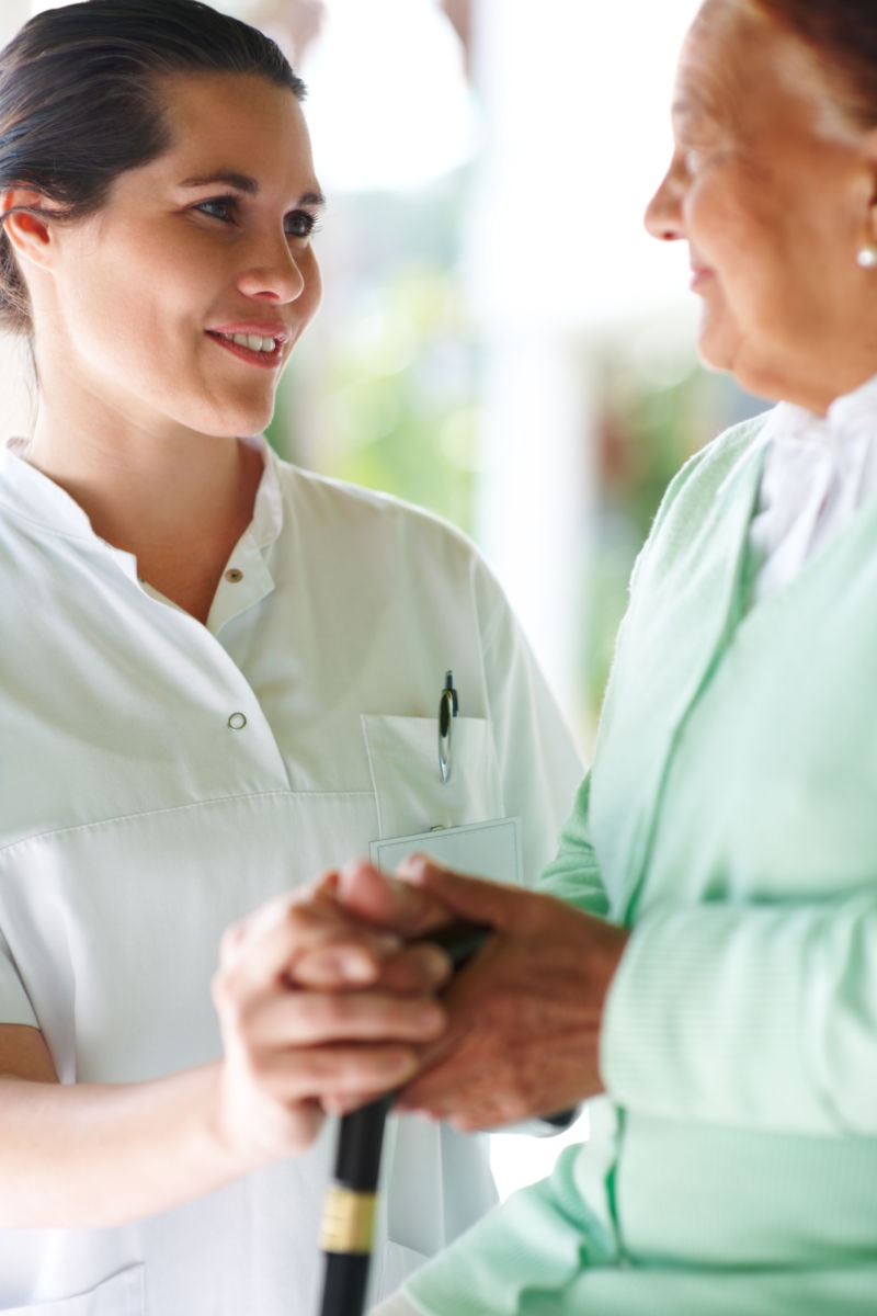 Young female nurse confronting an old patient